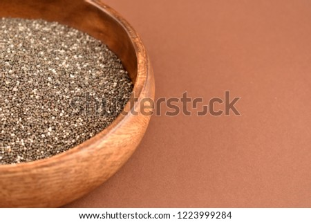 Chia seeds stock images. Healthy food isolated on a brown background. Chia seeds in a wooden bowl #1223999284