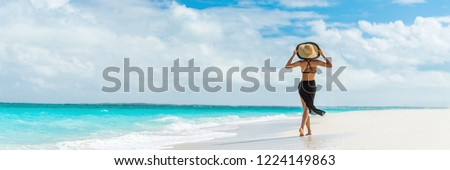 Luxury travel summer beach vacation woman walking in black beachwear skirt and hat on paradise white sand Caribbean beach. Lady tourist on Caribbean holiday vacation resort. Banner panorama landscape. #1224149863