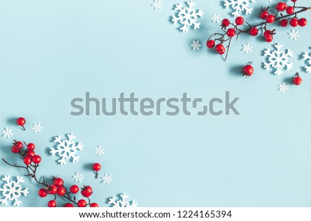Christmas or winter composition. Frame made of snowflakes and red berries on pastel blue background. Christmas, winter, new year concept. Flat lay, top view, copy space #1224165394