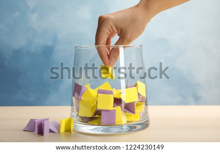 Woman taking paper piece from glass vase on table. Lottery #1224230149