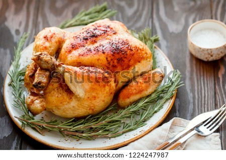 Whole grill chicken with caramelized skin and fresh rosemary on a wooden dinner table. #1224247987