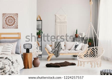 Bright living room interior with macrame on the wall, beige couch with pillow and blanket, hammock chair, fluffy rug and bedside table with lamp standing by the bed in the real photo #1224257557