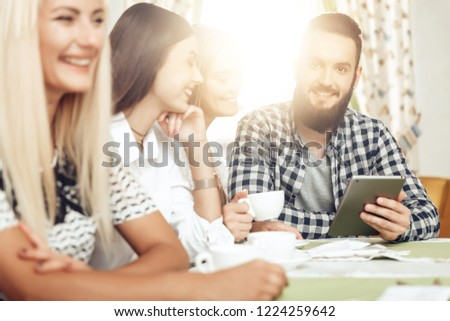 Happy friends are resting in cafe drinking coffee. A group of smiling men and women are sitting at a table in a cafe with a tablet. The guy looks at the tablet funny information that all the fun #1224259642