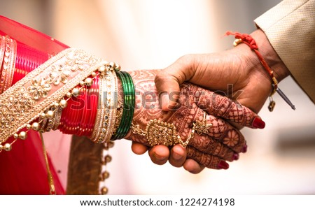 Indian Hindu Couple holding each other hands during their marriage symbolising love and affection. Hands of bride is decorated beautifully by indian mehndi art alongwith jewellery and colorful bangles #1224274198