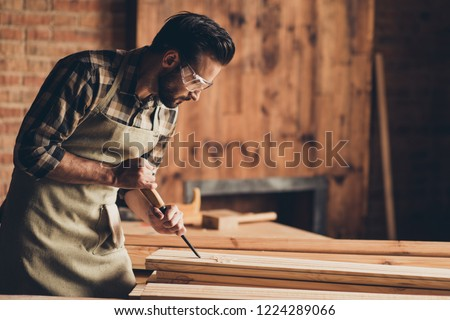 Half turned photo portrait of serious focused concentrated thoughtful handsome bearded strong masculine busy professional foreman builder using equipment wooden plank #1224289066
