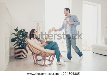 Profile side view portrait of nice cute lovely beautiful trendy stylish cheerful positive caucasian couple enjoying life spending free spare time guy giving cup to girl in modern apartments #1224304885