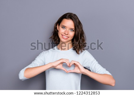 Beautiful nice attractive pretty charming lovely lady with her brunette hair she show heart symbol near chest stand isolated on gray wall make pretty smile