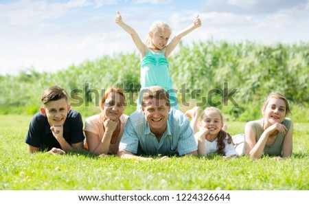 happy smiling mature couple with four different age children lying on the grass in park on summer day