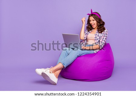Full size portrait of lady in checkered shirt denim jeans her brunette curly wave style stylish hair she sit isolated on violet purple trendy background work on notebook open mouth raised fist up