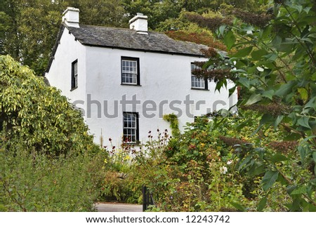 An English whitewashed cottage in a woodland setting #12243742