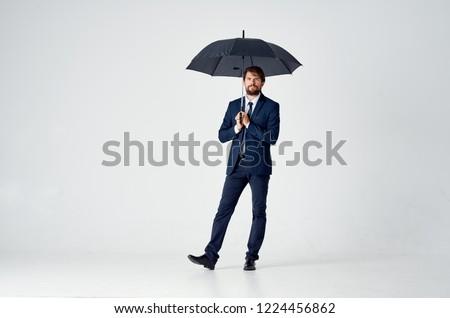 man in a suit standing under an umbrella                        #1224456862