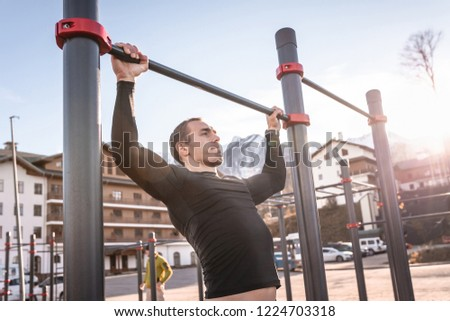 A young male athlete doing pull ups on a horizontal bar on the street on a sunny warm day. Concept of calisthenic and sports training. Workout lifestyle concept #1224703318