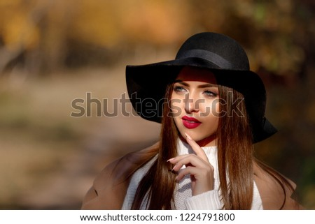 portrait of beautiful young woman in black hat in park in the autumn #1224791800