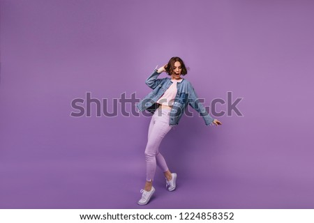 Full-length portrait of attractive slim girl wears white sport shoes. Indoor photo of enchanting caucasian woman dancing on violet background. #1224858352