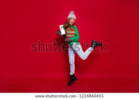 Full-lenght portrait of happy stylish young lady dressed green sweater, blue jeans, black boots and grey winter cap jumping with new year presents on isolated red background #1224860455