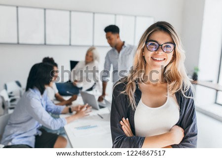 Blonde female executive posing with smile and arms crossed during brainstorm with managers. Indoor portrait of european student spending time in hall with asian and african friends. Royalty-Free Stock Photo #1224867517