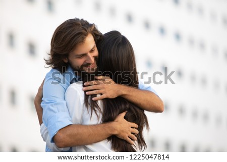 Happy Caucasian man hugging his friend outdoors. Professional successful couple embracing on urban street. Togetherness concept #1225047814