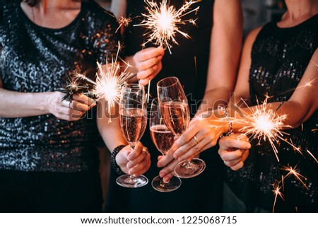 Friends celebrating Christmas or New Year eve party with Bengal lights and rose champagne. #1225068715