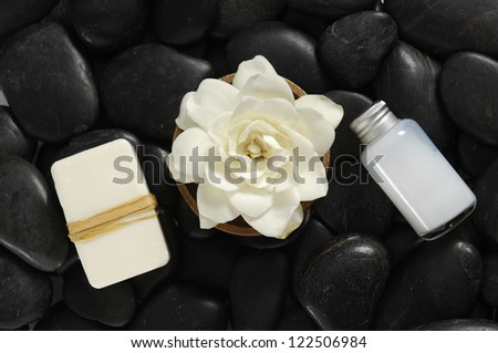 gardenia flower with wooden bowl with salt in glass, soap on black pebbles #122506984