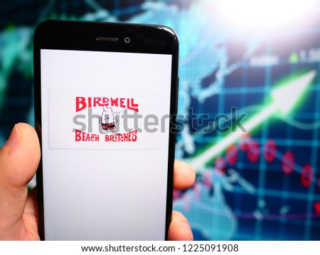 Murcia, Spain; Nov 7, 2018: Birdwell Beach Britches logo in phone with earnings graphic on background. Birdwell Beach Britches is an American surf clothing company  #1225091908