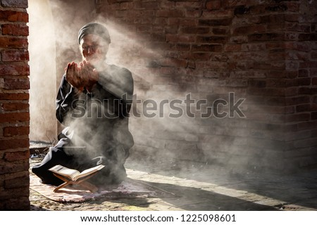 Silhouette of muslim man having worship and praying for fasting and Eid of Islam culture in old mosque with lighting and smoke background Royalty-Free Stock Photo #1225098601