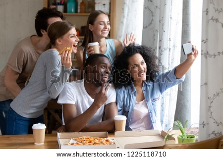Happy diverse friends make selfie photography on smartphone during lunch. Students eating pizza and drinking coffee together indoors. Leisure activities friendship between multi-ethnic people concept #1225118710