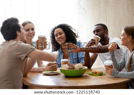 Diverse friends girls and guys sitting around table chatting having fun drink coffee in paper cups enjoy time together. Friendship between different race multinational young millennial people concept #1225118740
