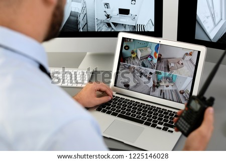Male security guard with portable transmitter monitoring home cameras indoors, closeup #1225146028