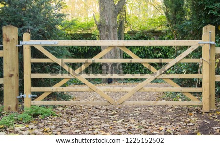 A five bar wooden gate goes through a fence leding onto a path through a wood #1225152502