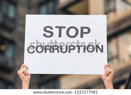 Woman holding placard with text STOP CORRUPTION outdoors #1225177981