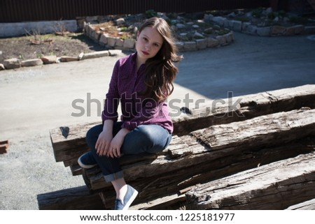 girl sitting on logs #1225181977