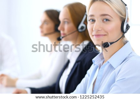 Call center. Group of operators at work. Focus at blonde business woman in headset #1225252435