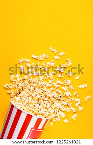 One time use carton bucket with red white stripes, blank space for text full of pop corn, scattered on table. Copy space, close up, top view, background. Cinema theater promo concept. #1225261021