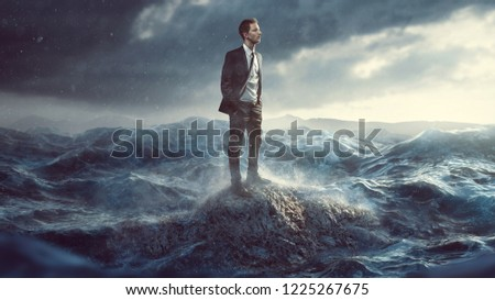 Businessman standig on a rock in the surf #1225267675