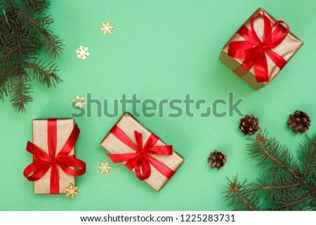 Christmas decoration. Gift boxes, fir tree branches with cones and decorative snowflakes on green background. Top view. Christmas greeting card concept. #1225283731