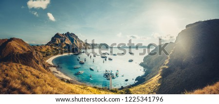 Mountains, bay, sun rays. Aerial shot. Padar. Wonderful panoramic overview the cute bay with the sand beaches surrounded by the mountains. Landscape of Padar island. Komodo National Park. Indonesia.