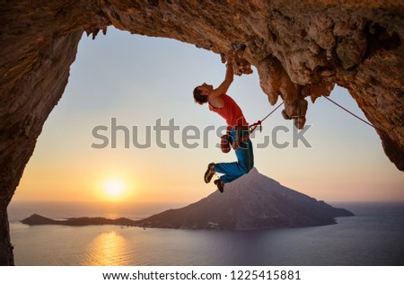 Male rock climber hanging with one hand on challenging route on cliff at sunset #1225415881