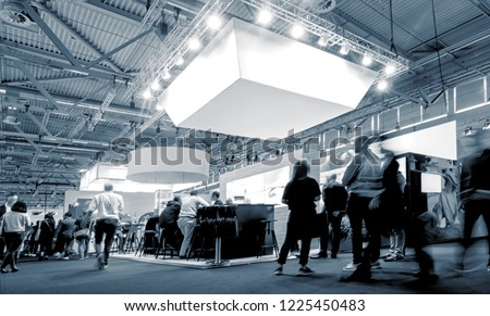 business people walking between trade show booths at a public event exhibition hall Royalty-Free Stock Photo #1225450483