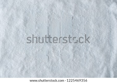 White wooden table background with snow. Winter or Christmas top view. Minimal flat lay.