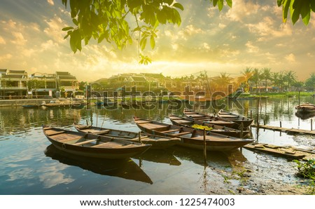 Wooden boats on the Thu Bon River in Hoi An Ancient Town,  Vietnam. Yellow old houses on waterfront reflected in river. Vietnam  Royalty-Free Stock Photo #1225474003