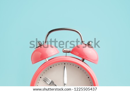 Alarm clock. Fork and knife instead of clock hands. Concept of intermittent fasting, lunchtime, diet and weight loss #1225505437