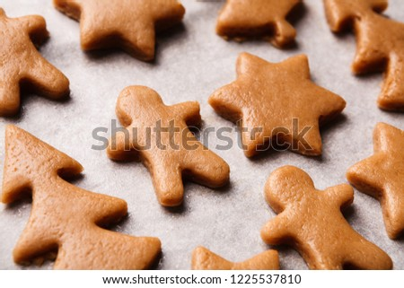 Raw gingerbread cookies. Christmas figures from dough on paper, prepared for baking in oven, closeup #1225537810