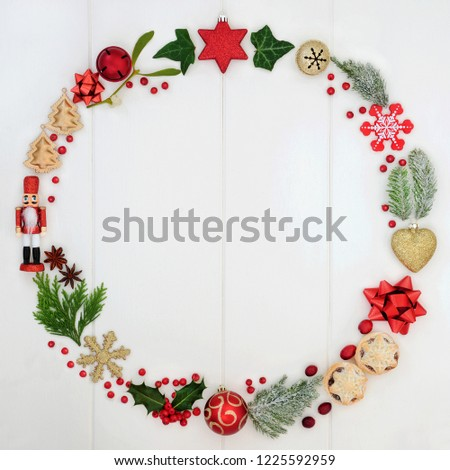 Abstract Christmas wreath garland with a selection of traditional symbols including food, flora and bauble decorations on rustic white wood background. Top view. #1225592959