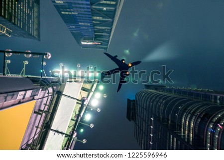 Plane Flying Over New York City At Night With Electric Sky Rise Buildings #1225596946