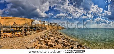 HAMMAMET, TUNISIA - OCT 2014: Cafe on stony beach of ancient Medina on October 6, 2014 in Hammamet, Tunisia #1225720039