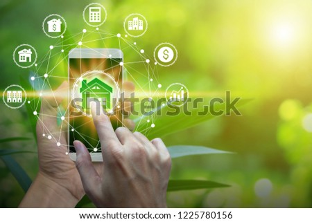 Hand use smartphone with property investment icons over the Network connection on property background, Property investment concept. #1225780156