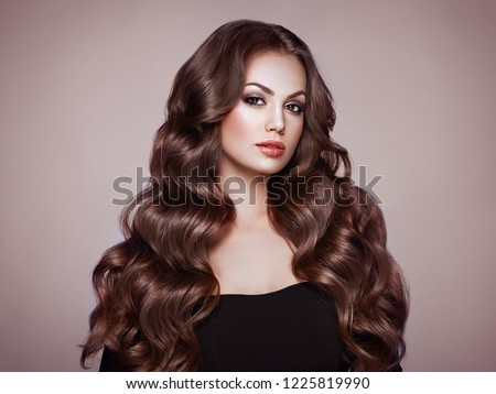 Brunette Girl with Long Healthy and Shiny Curly Hair. Care and Beauty. Beautiful Model Woman with Wavy Hairstyle. Make-Up and Black Dress #1225819990