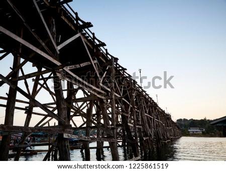 Beautiful sunset scene at old an long wooden bridge Asian wooden bridge Kanchanaburi province, Thailand #1225861519