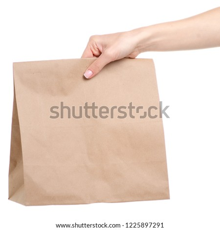 Paper bag package in hand on white background isolation #1225897291