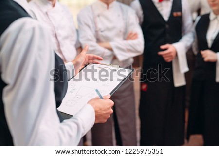 restaurant manager and his staff in kitchen. interacting to head chef in commercial kitchen #1225975351